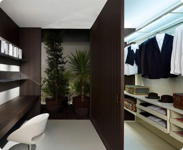 В комнате прямоугольной конфигурации можно смонтировать перегородку из гипсокартона, разделяющую базовую часть помещения от хранилища одежды. Если установить зеркальные двери, можно сохранить визуальный простор комнаты.