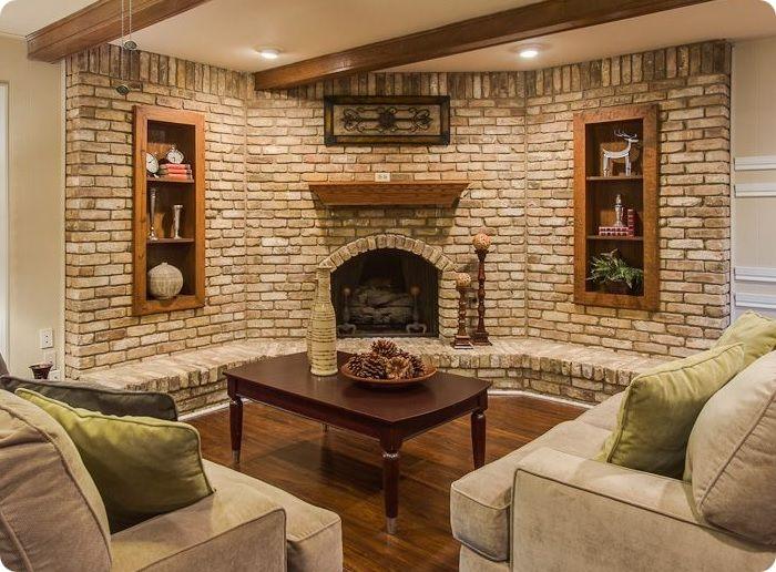 Кирпичная кладка в интерьере гостиной с угловым камином.