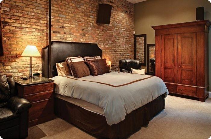 Тёплый оттенок кирпича в спальне прекрасно гармонирует с массивной мебелью .