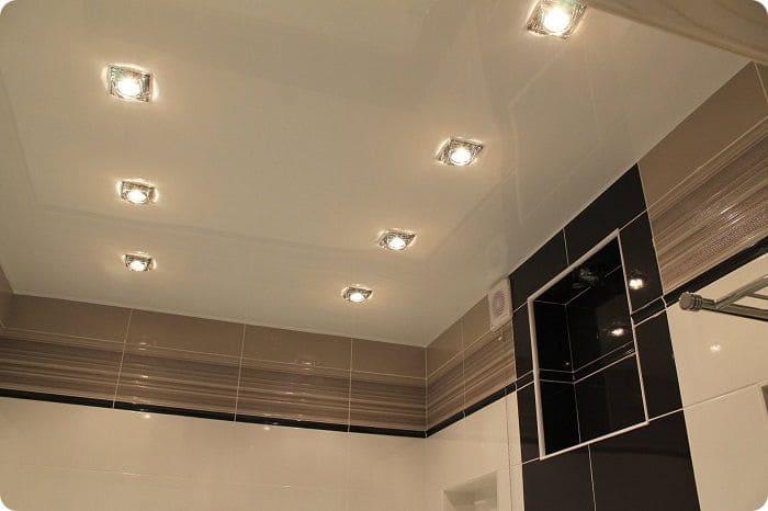Точечные светильники на глянцевом натяжном потолке.