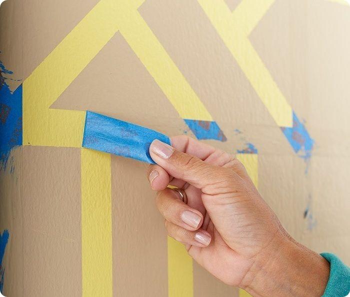 На обработанную стену наклеивают малярный скотч таким образом, чтобы образовались геометрические фигуры.