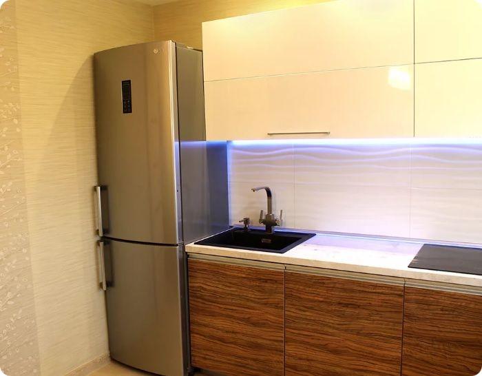 Установка холодильника в углу подходит при условии, что длина стены не менее 5 метров. В этом случае по одной линии можно установить не только холодильник, но и плиту, мойку, столешницу, другую бытовую технику. Холодильник нужно отделить от плиты хотя бы небольшим столом.