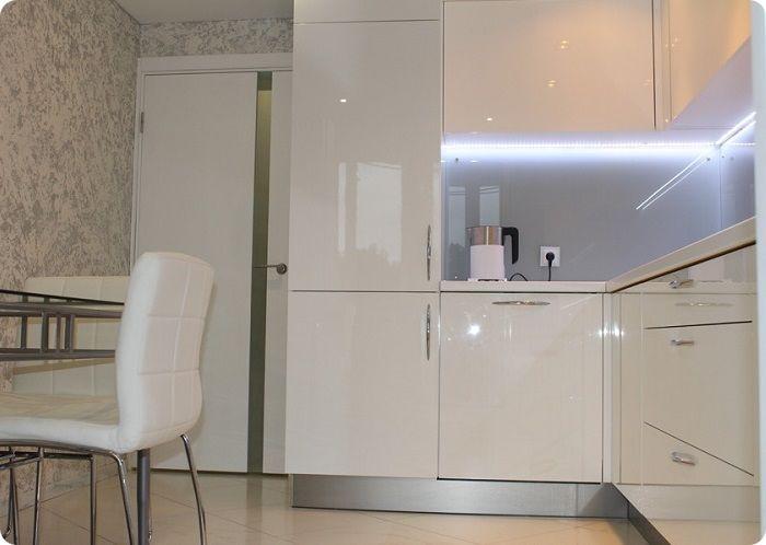 Белый встроенный холодильник на небольшой кухне.