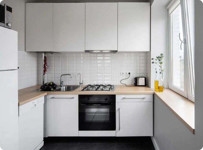 Угловая мебель не слишком компактна, но вместительна. Большой холодильник лучше разместить в одной из точек воображаемого треугольника — у окна в углу помещения либо у входа.
