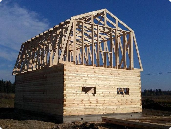 Строящийся дом с мансардной ломаной крышей.