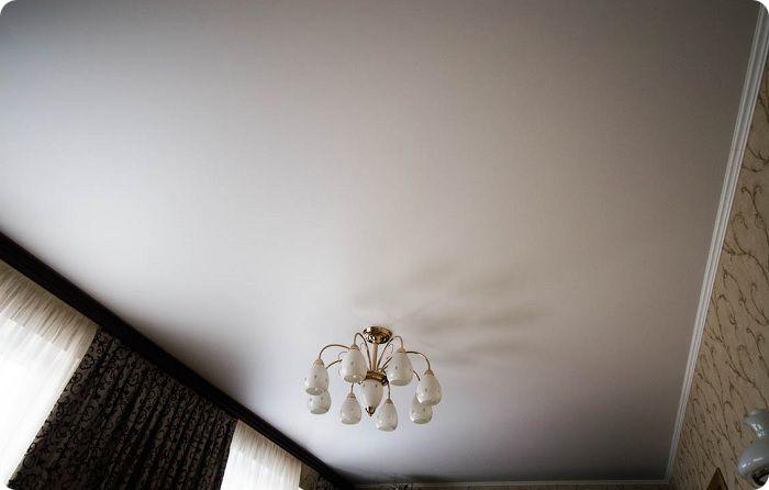 Белый текстильный натяжной потолок.