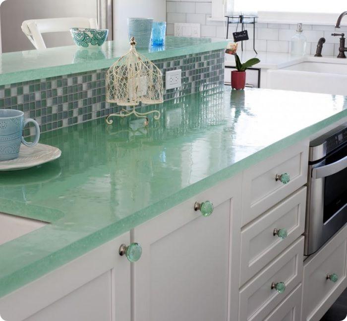 Обеденную зону можно выделить столом со столешницей из стекла, с расставленными вокруг него зелёными стульями.