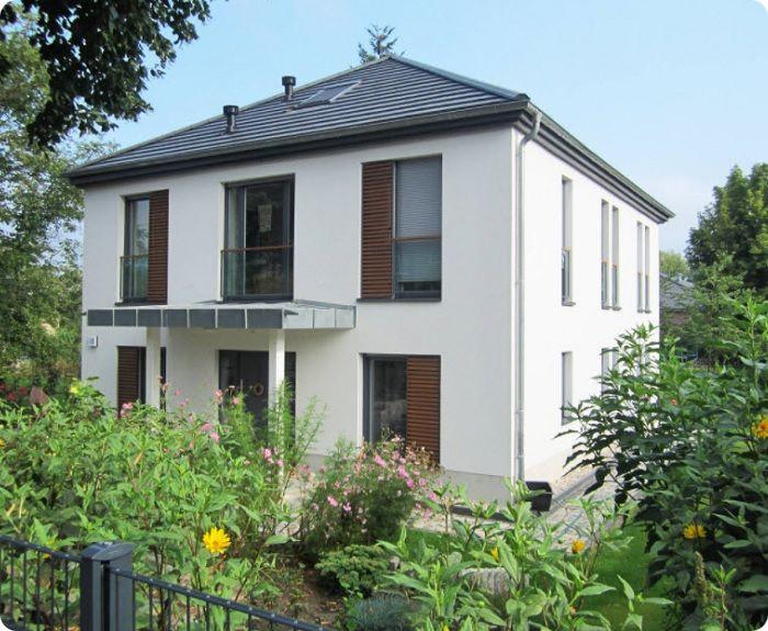 Двухэтажный дом с четырёхскатной крышей.