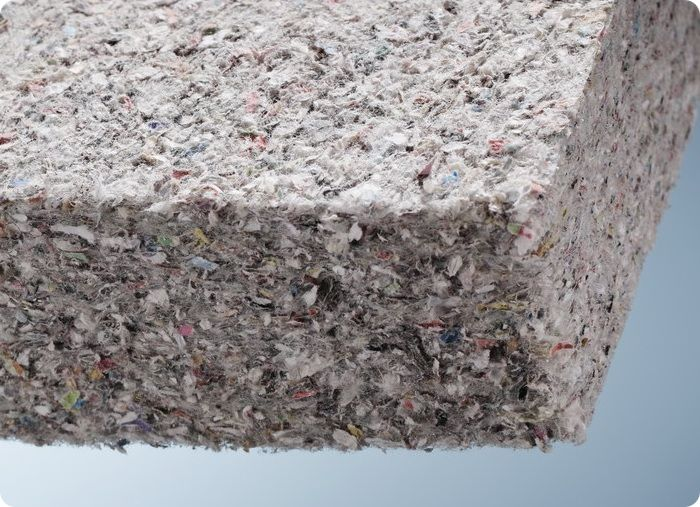 Целлюлозный утепляющий материал (эковата) выглядит как рыхлое и невесомое волокнистое полотно серого оттенка.