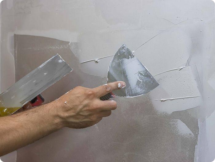 Маленьким инструментом набирают немного смеси и накладывают на большой шпатель. Затем раствор равномерно распределяют по всей поверхности.