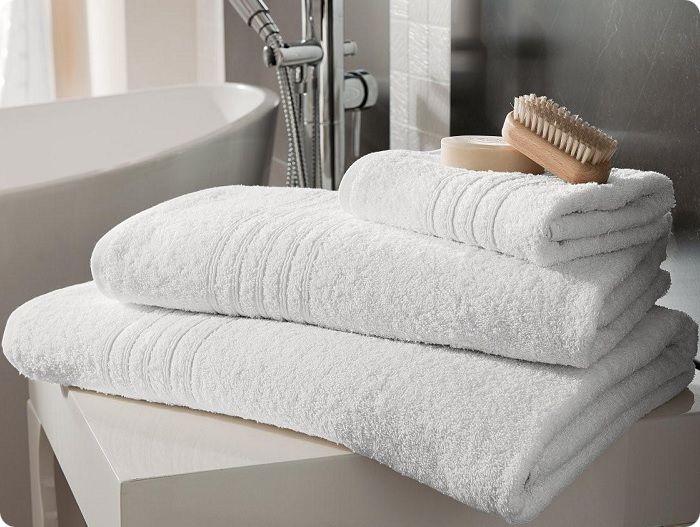 Аккуратно сложенные на полке махровые полотенца создают уютную обстановку.