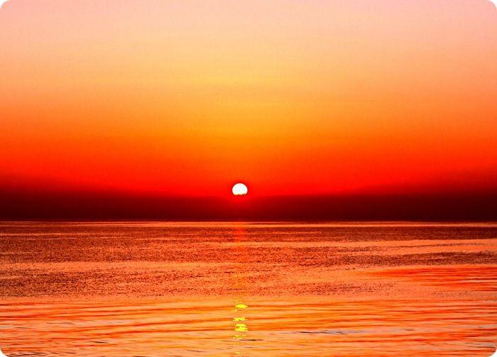 Закат солнца в песочной палитре, которая плавно, но быстро меняется оранжевыми, затем красными тонами, а в точках, расположенных в непосредственной близости от горизонта — бурыми красками на контрасте седеющего неба.