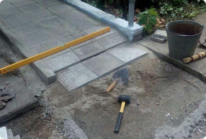 Плитка, уложенная на бетонное основание и инструменты.